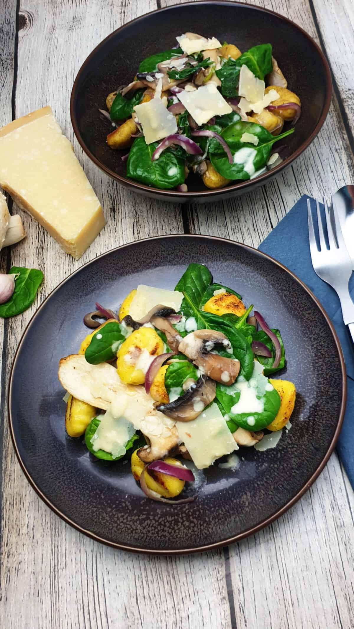 Auf einem braunen Teller angerichtet ein Gnocchi Salat mit Spinat. Im Hintergrund Deko.