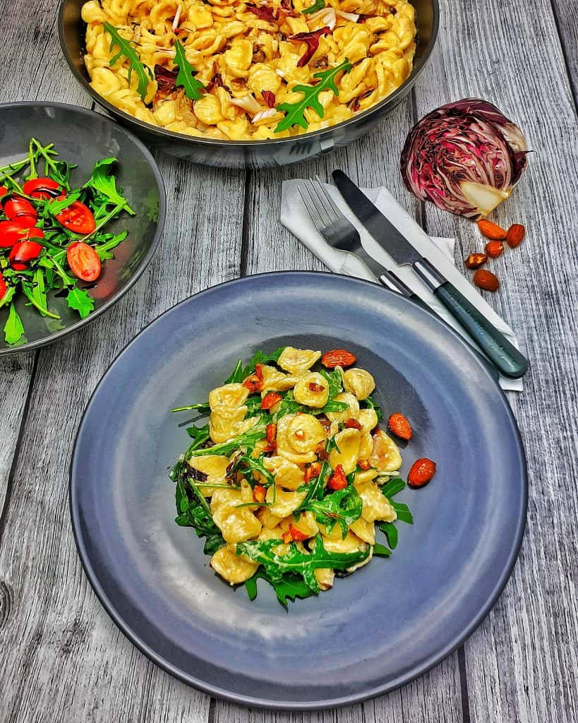 Auf einem grauen Teller angerichtet Italienische Nudeln - Orecchiette mit Macarpone und Rucola. Im Hintergrund eine Pfanne mit demselben Gericht und neben dem Teller eine Schale mit grünem Salat.