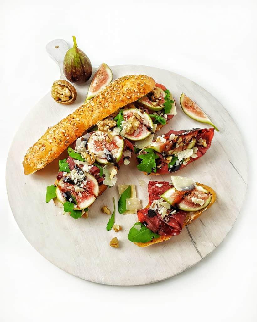 Auf einem hellen Brett angerichtet ein Dinkel-Parmesan-Baguette mit Schinken und Feigen.