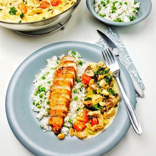 Auf einem grauen Teller angerichtet Hähnchen mit Erbsen-Reis und Gemüse in einer cremigen Soße. Im Hintergrund Deko.