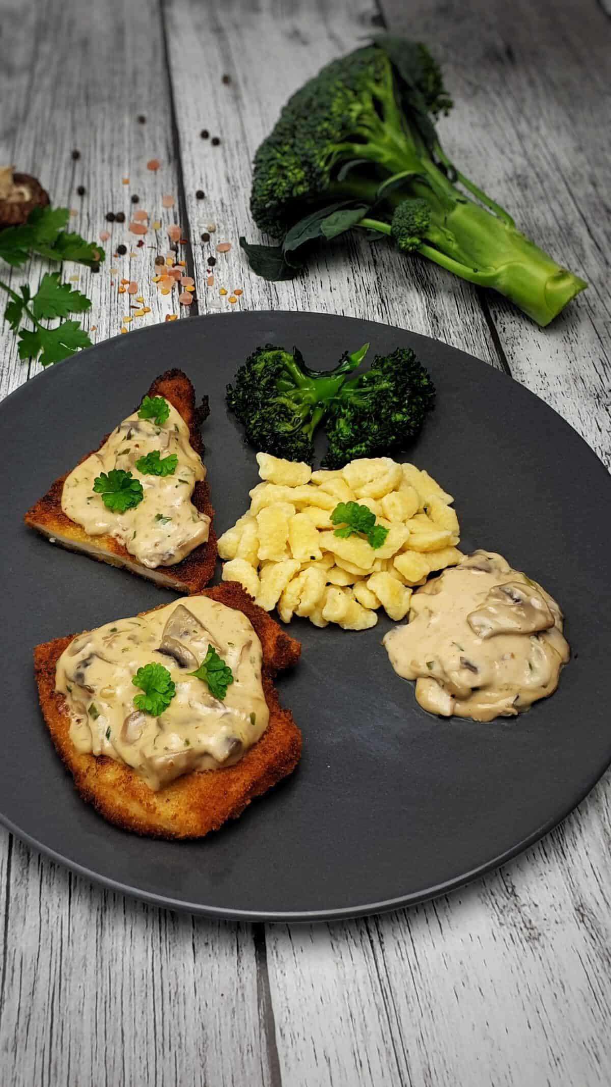 Auf einem dunkelgrauen Teller angerichtet Champignons Rahm Soße mit Schnitzel und Spätzle.