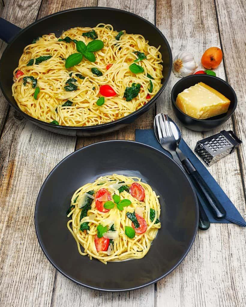 Schnelle Spaghetti-Pfanne mit Frischkäse und Tomaten in einer braunen Schale angerichtet. Im Hintergrund Deko.