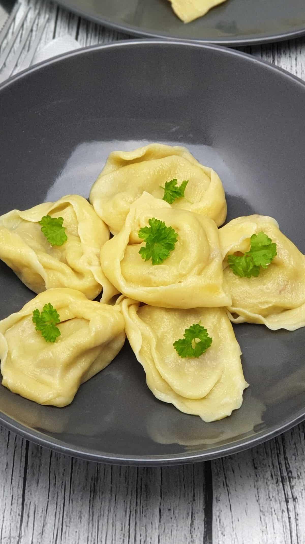 Gefüllte Teigtaschen auch Wareniki genannt auf einem grauen Teller serviert. mit Petersilie bestreut.
