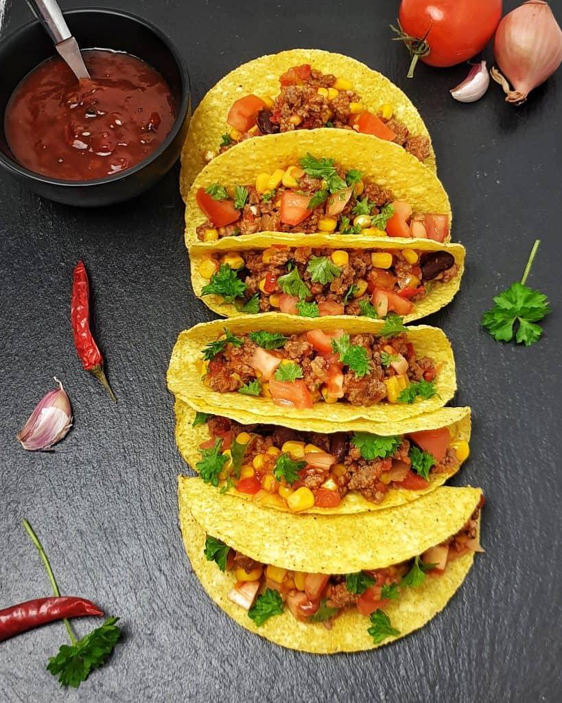 Gefüllte Taco Shells mit Chili con Carne auf einem Schieferbett.