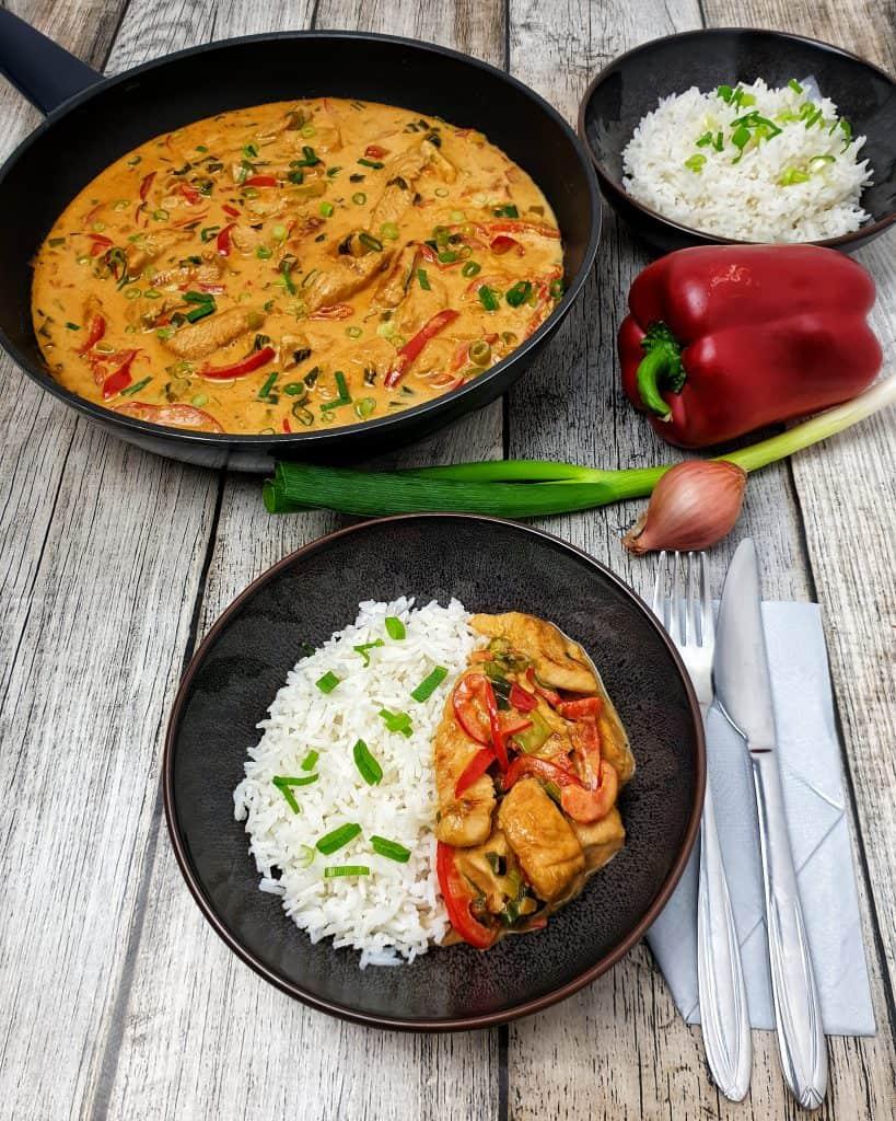 Puten-Curry mit Gemüse in einer braunen Schale mit Reis serviert und mit Frühlingszwiebeln bestreut.