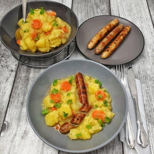 Kartoffelgemüse mit grober Bratwurst auf einem grauen Teller angerichtet.