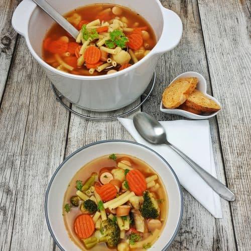 In einer weißen Schale angerichtet eine Gemüse-Nudel-Suppe mit Bockwurst. Im Hintergrund ein weißer Keramik-Topf mit Suppe.