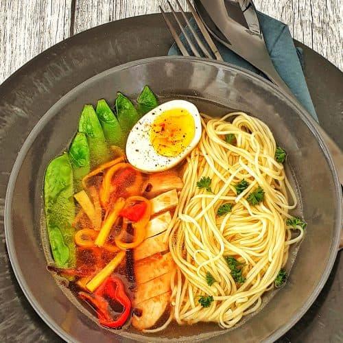 In einer grauen Schale angerichtet einen Hähnchen Ramen-Suppe mit Gemüse, Ei und Nudeln.