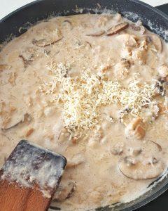In einer Pfanne eine helle Sahne Soße mit Hähnchen.