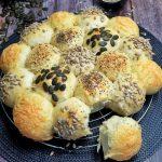 Brotsonne, bestehend aus kleinen Brötchen, zu einer Sonne gelegt und mit verschiedenen Körnern und Käse bestreut