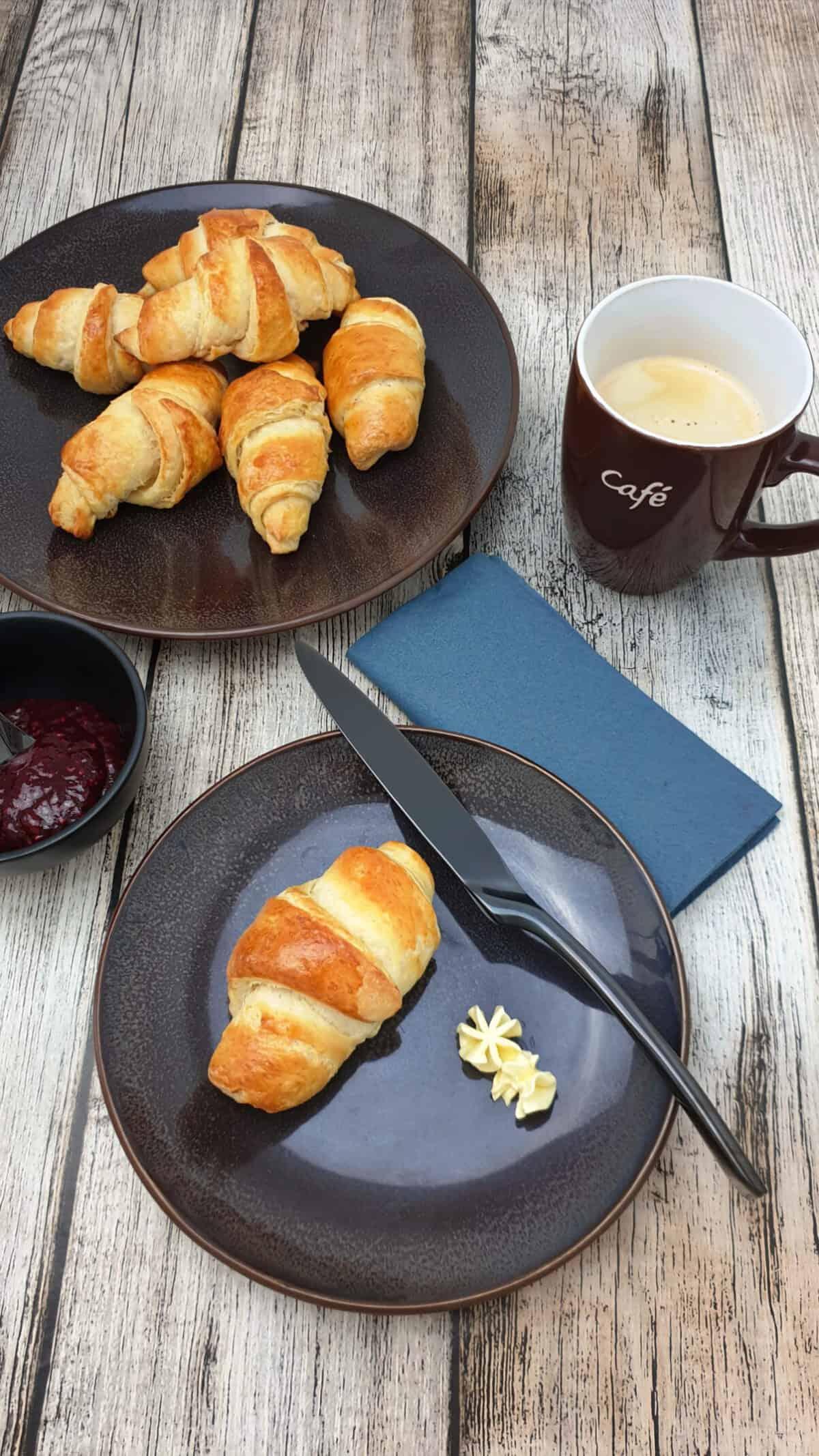 Auf einem braunen Teller ein selbst gemachtes Croissant. Im Hintergrund ein zweiter Teller mit fünf Croissants und Deko.
