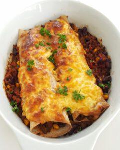 In einer weißen Auflaufform gefüllte und mit Käse überbackene Enchiladas.