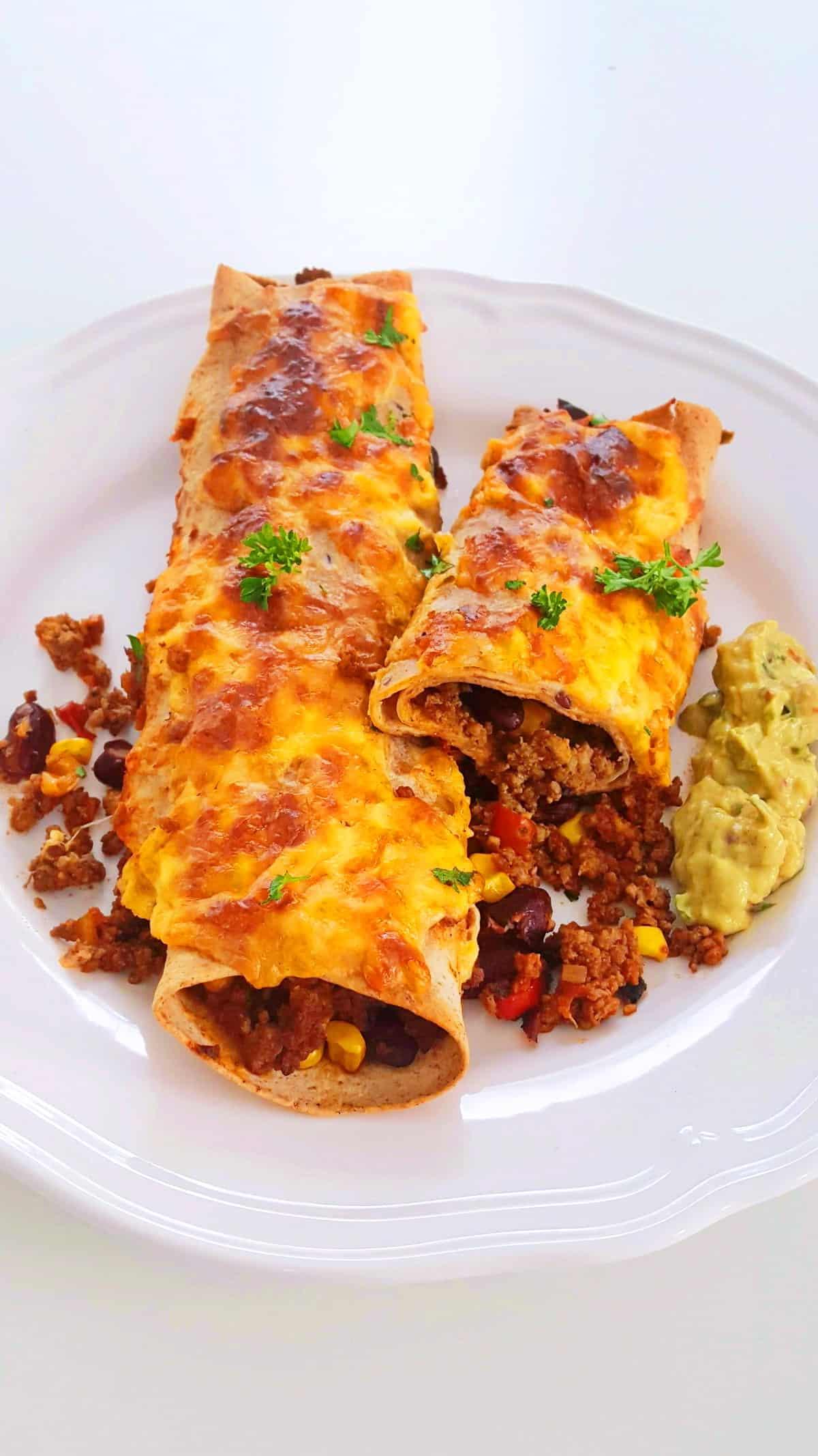 Enchiladas mit Hackfeisch gefüllt und überbacken auf einem weißen Teller.