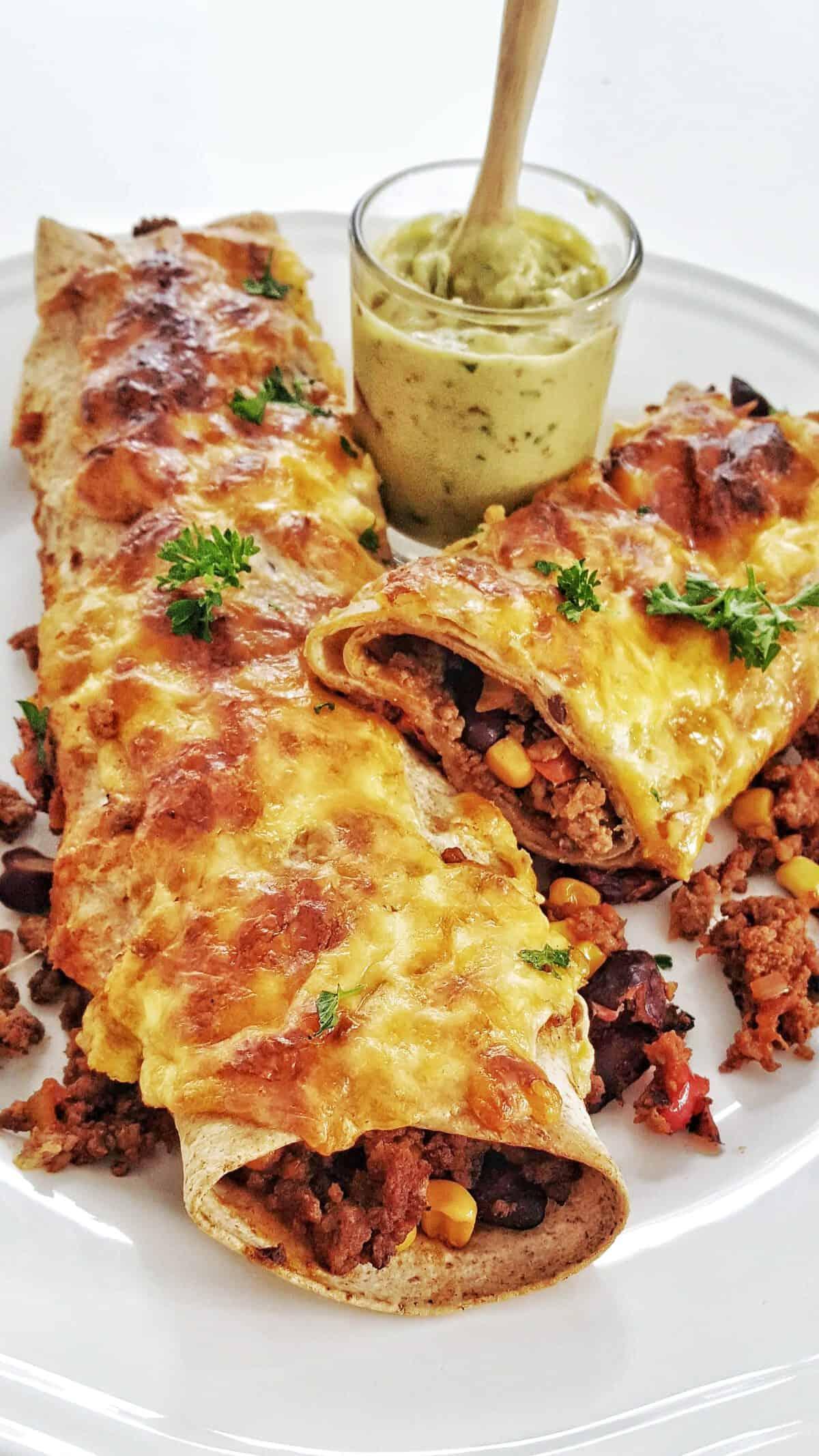 Auf einem weißen Teller angerichtet überbackene und mit Hackfleisch gefüllte Enchiladas. Mit Petersilie bestreut.