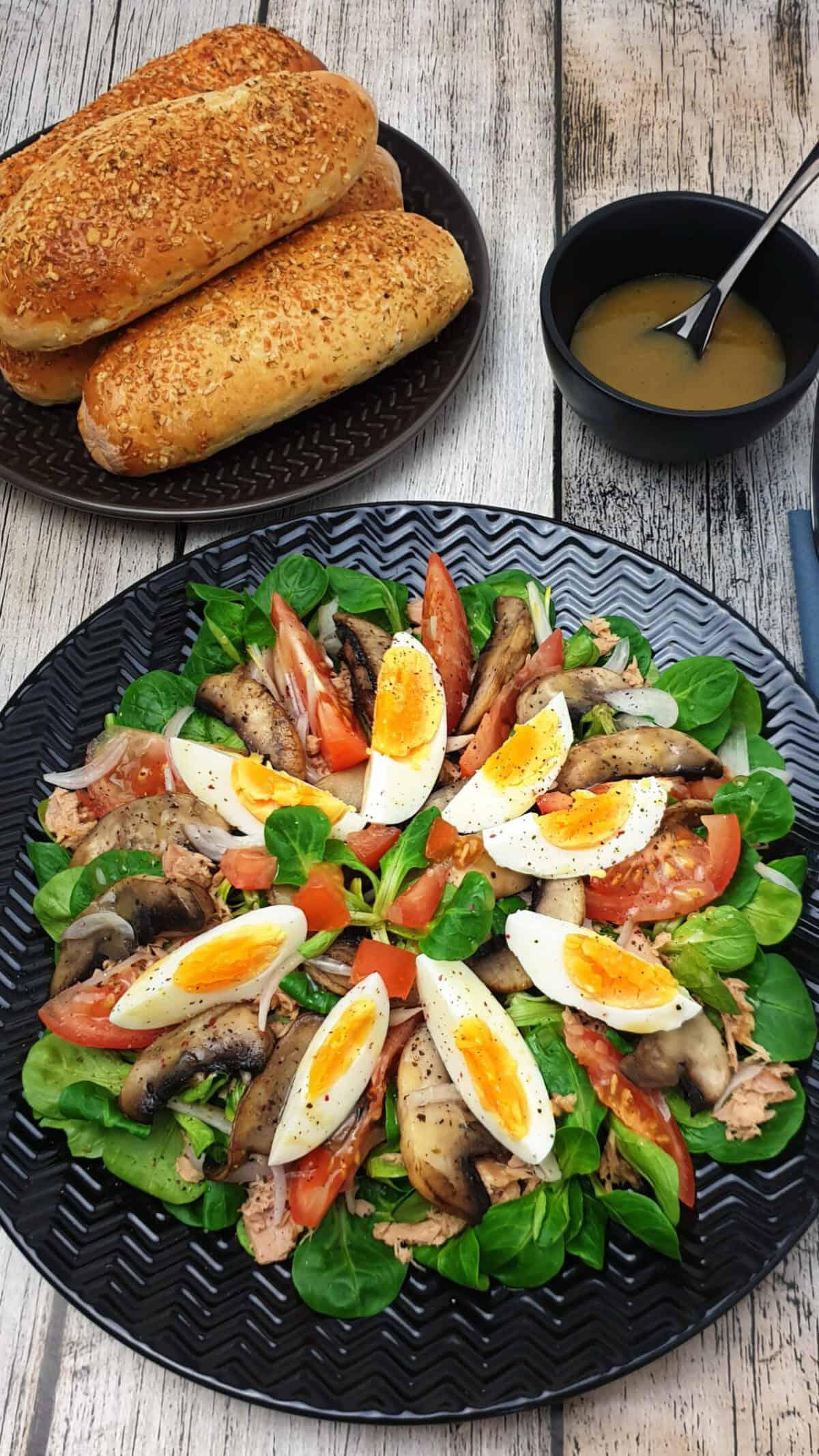 Auf einem schwarzen Teller angerichtet ein bunter Feldsalat mit Honig Senf Dressing, Thunfisch und Ei. Im Hintergrund Deko.