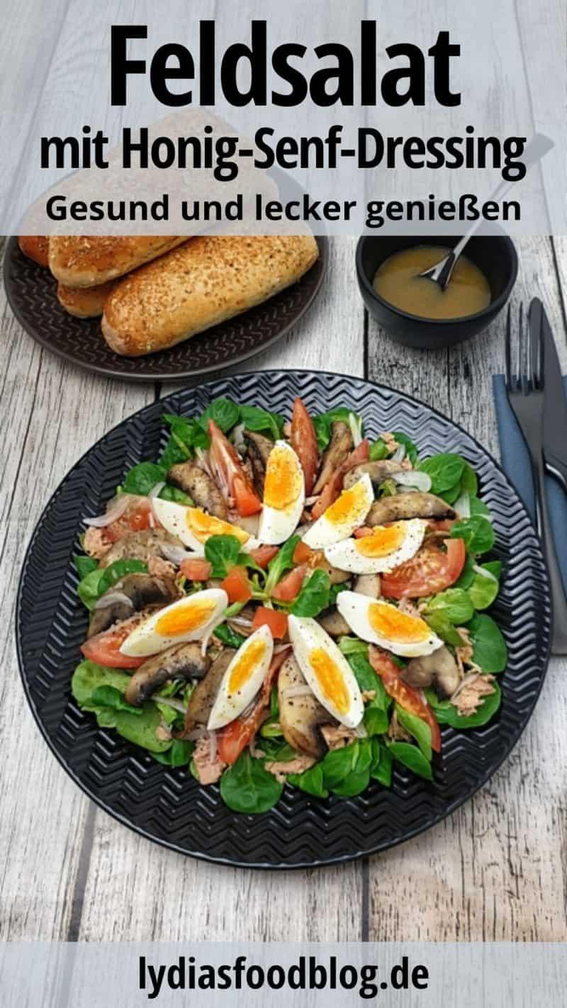 Ein frischer Salat auf einem schwarzen Teller angerichtet, mit Ei, Thunfisch, Feldsalat und Honig Senf Dressing