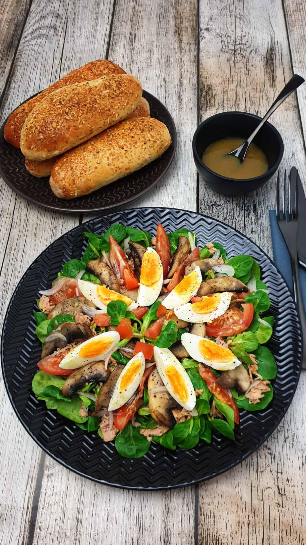 Auf einem schwarzen Teller angerichtet ein Feldsalat mit Honig Senf Dressing und Thunfisch. Im Hintergrund ein Teller mit frischen Baguettes,