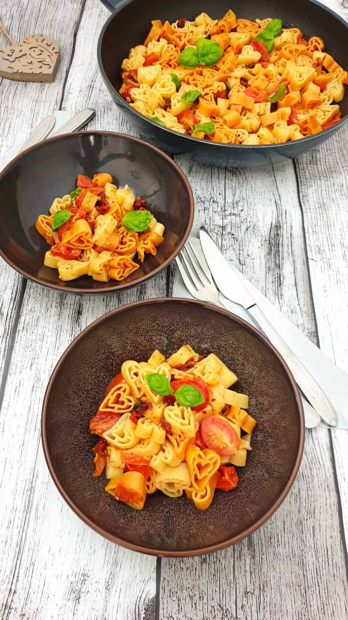 Herzchen Pasta mit einfacher Tomatensoße in einer braunen Schale angerichtet. Mit Basilikum bestreut. Im Hintergrund Deko.