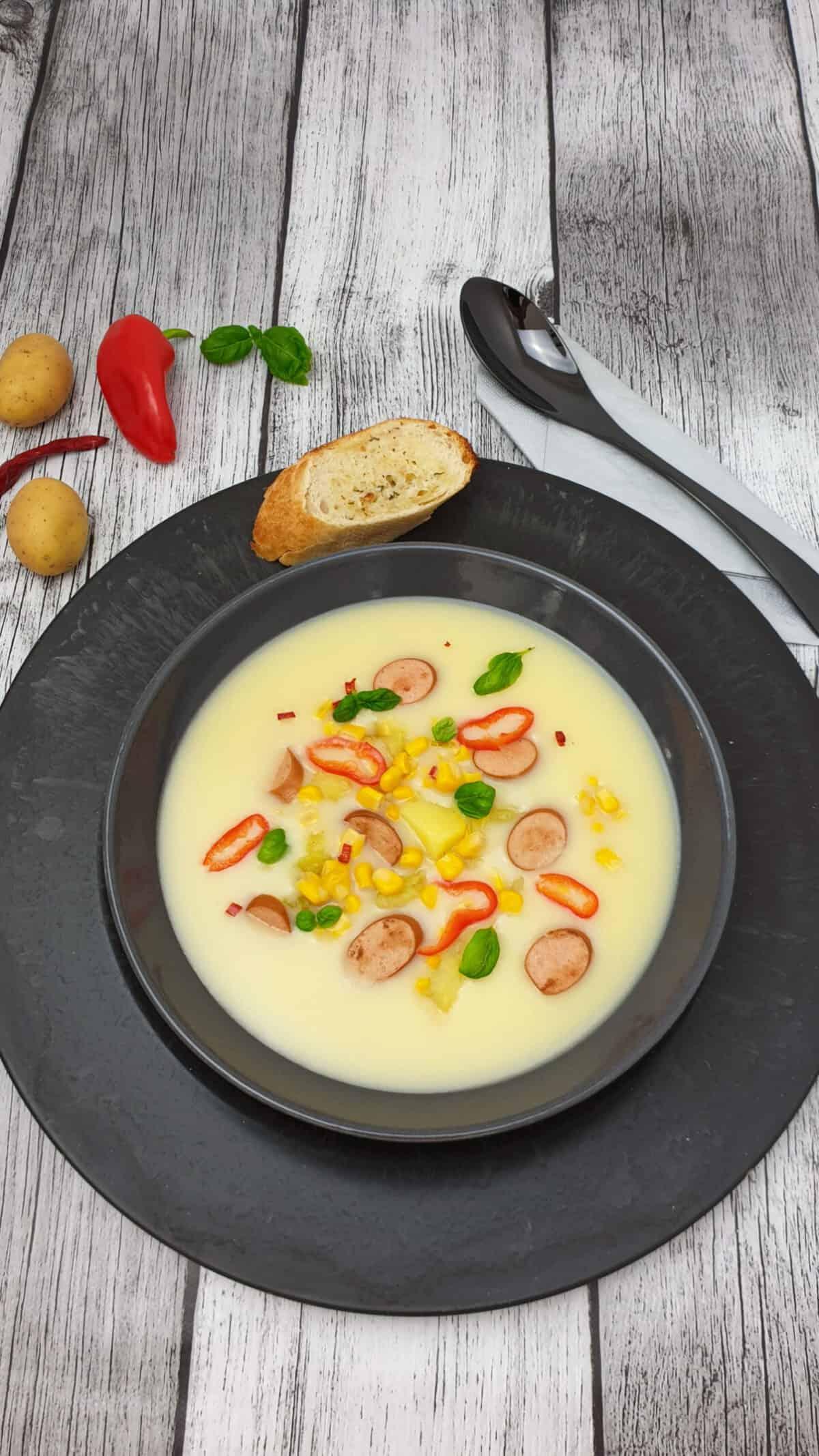 In einer grauen Schale eine Kartoffel-Mais-Suppe mit Würstchen. Daneben eine Scheibe Baguette. Im Hintergrund Deko.