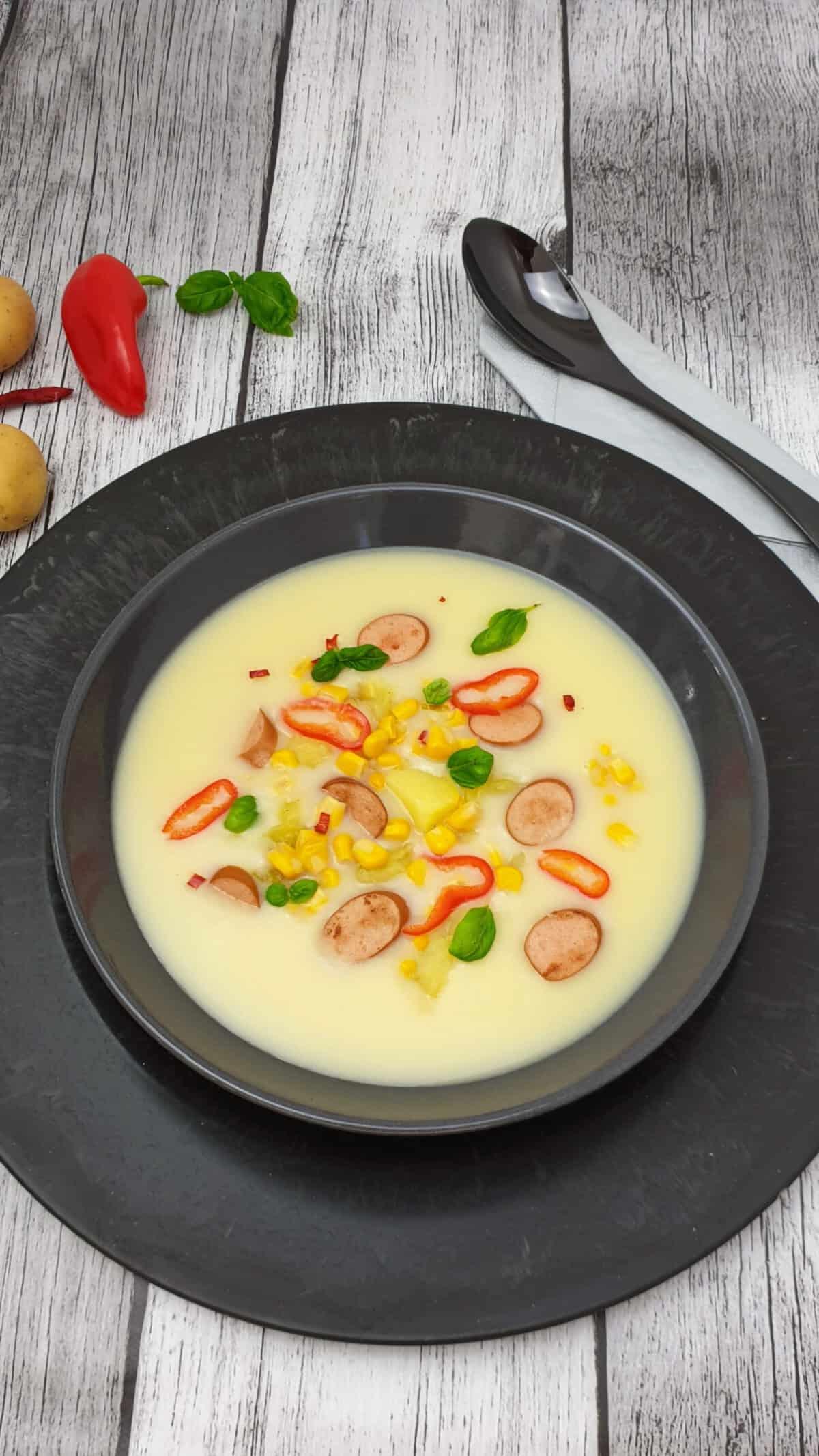 In einer grauen Schale eine Kartoffel-Mais-Suppe mit Würstchen. Im Hintergrund Deko.