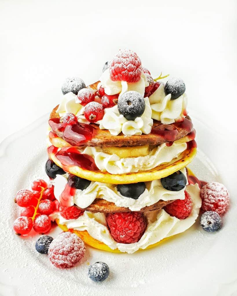 Auf einem weißen Teller Pancakes mit Sahne und frischen Früchten.
