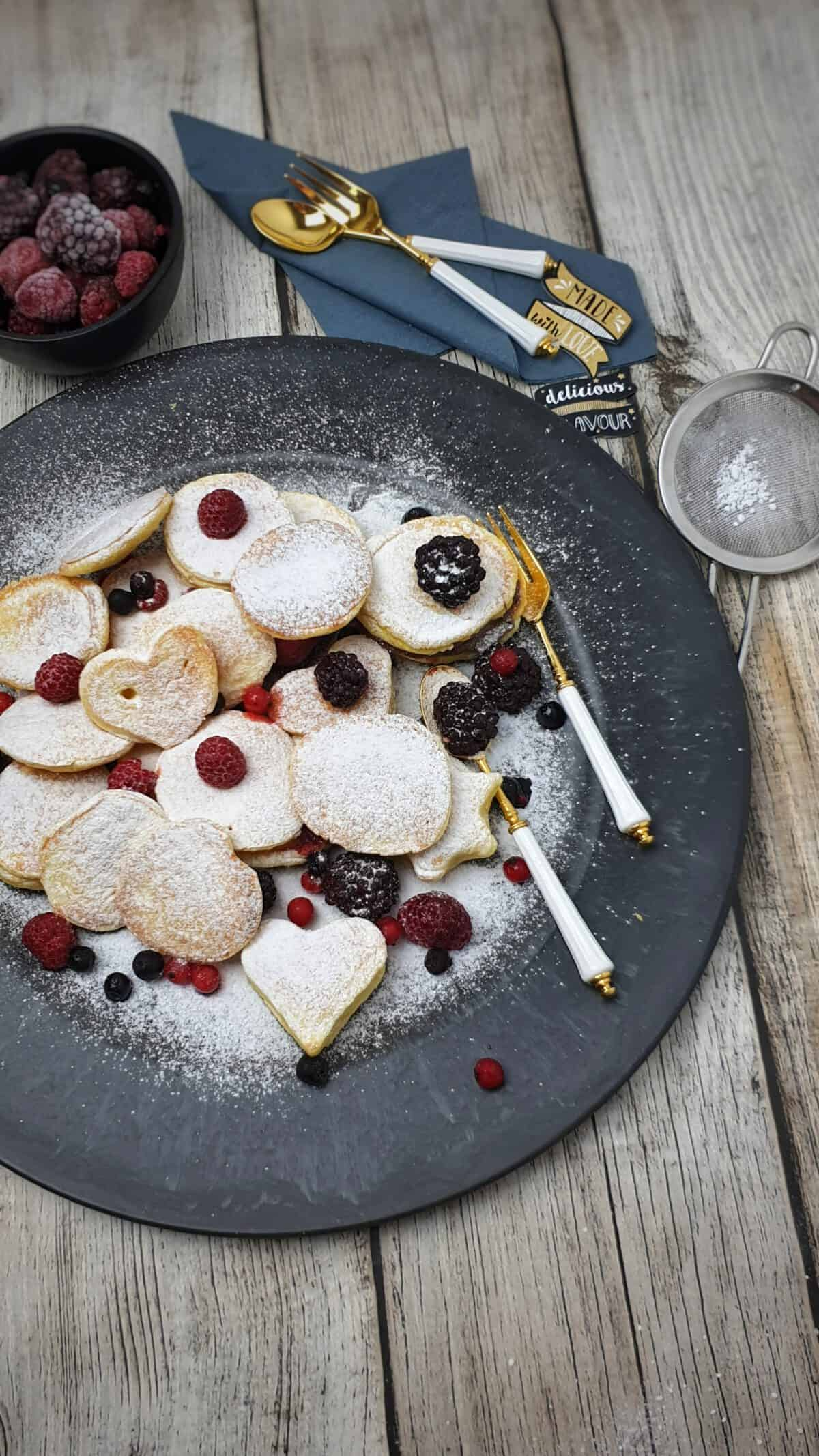 Auf einem dunklen runden Teller serviert Poffertjes mit Puderzucker und frischen Beeren.