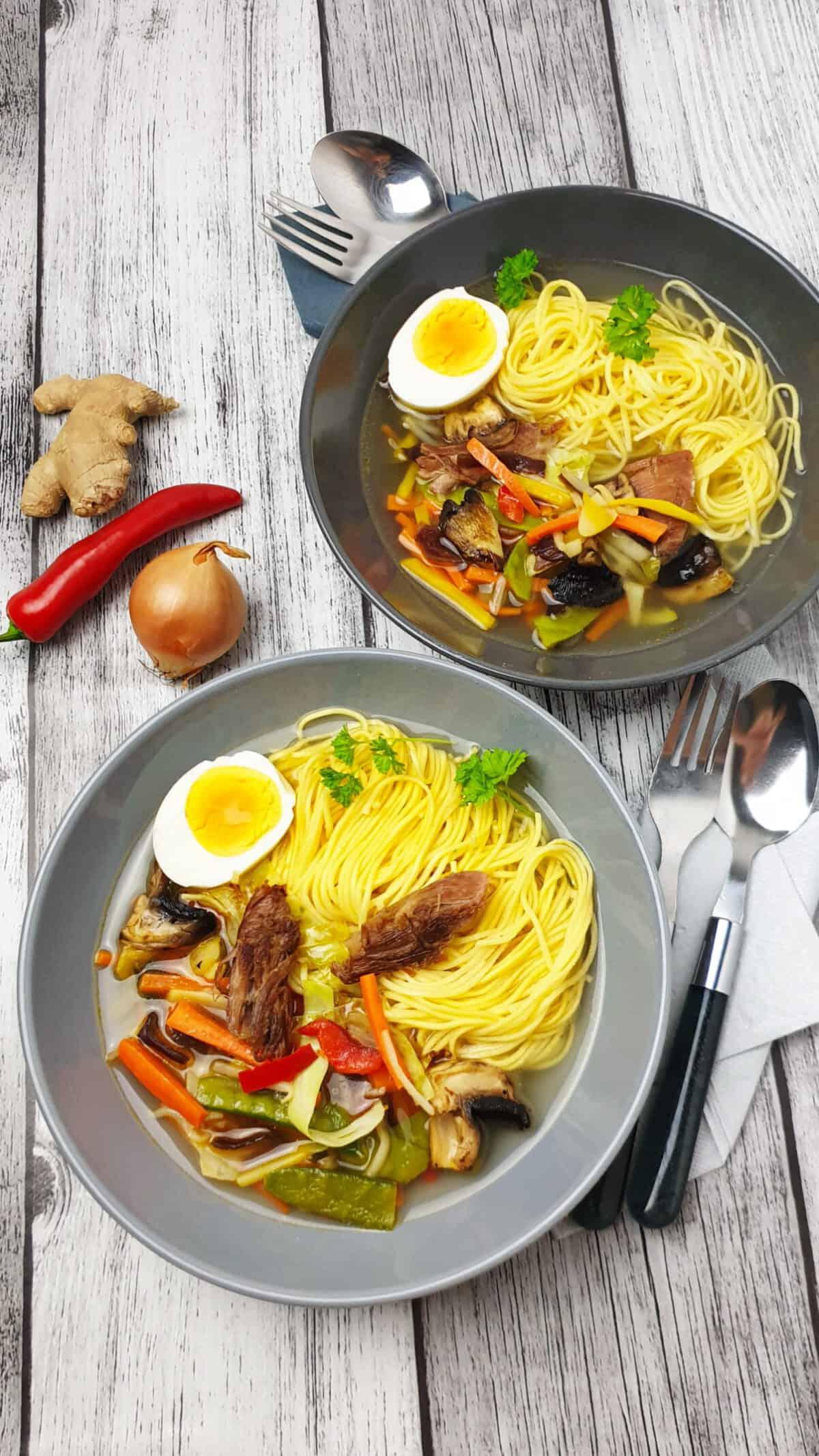 In einer grauen Schale eine Ramen-Suppe Huhn, Gemüse und Nudeln und einem halbiertem Ei.