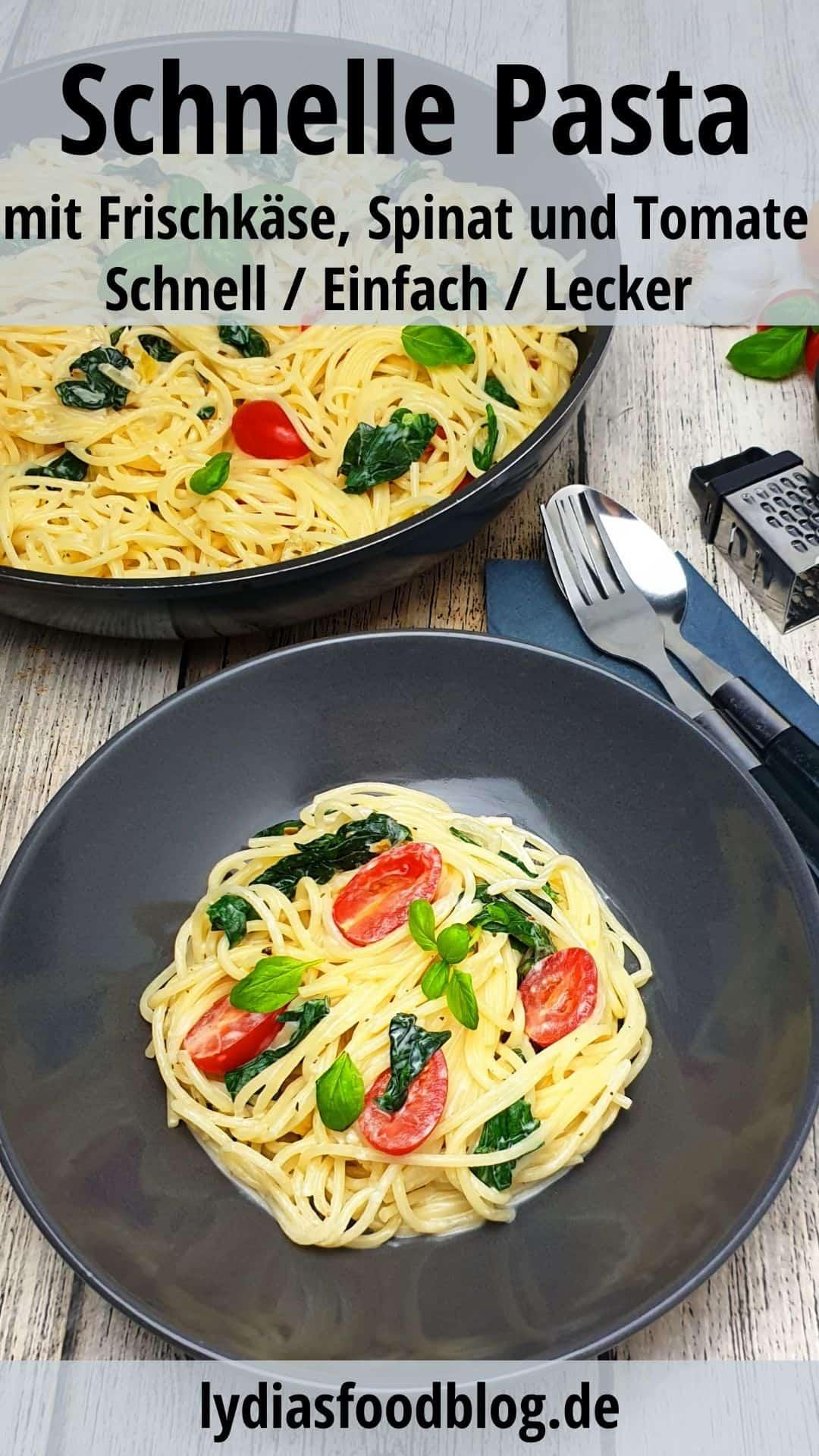 In einer grauen Schale ein Spaghetti Gericht mit Spinat und Tomate. Im Hintergrund Deko.