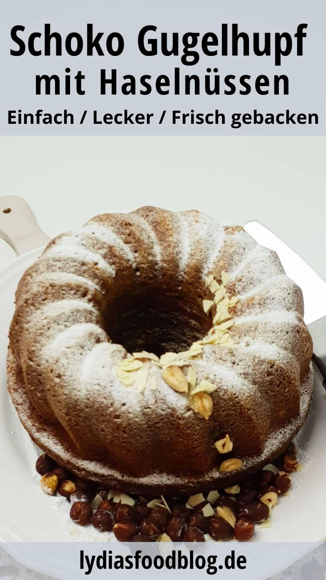 Ein Schoko Gugelhupf mit Haselnuss angerichtet auf einem weißen Teller mit Nüssen drumherum.