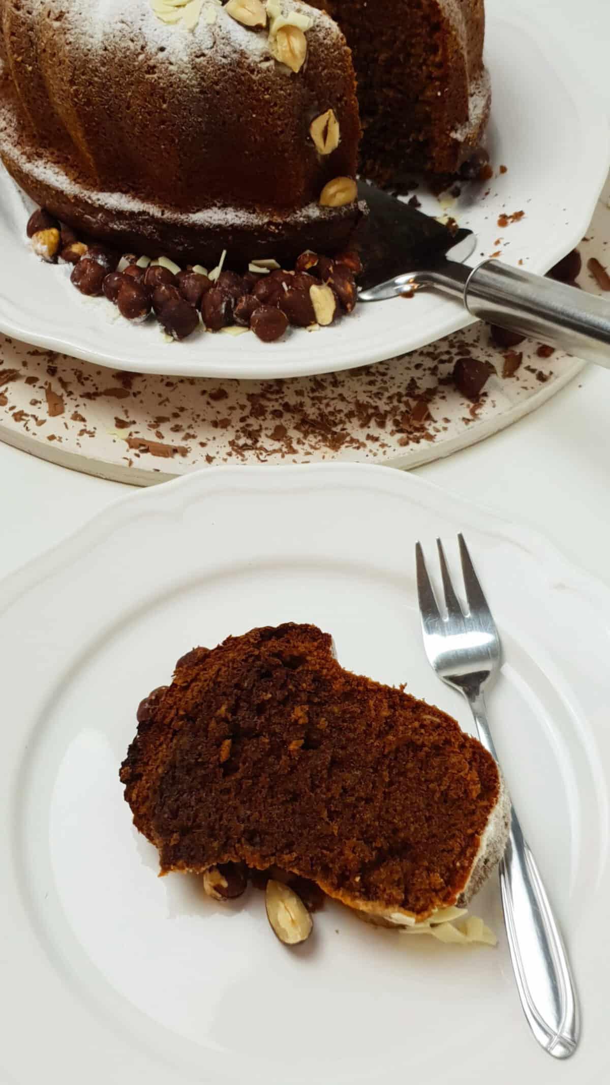 Auf einem weißen Teller ein Schoko Gugelhupf mit Nüssen.