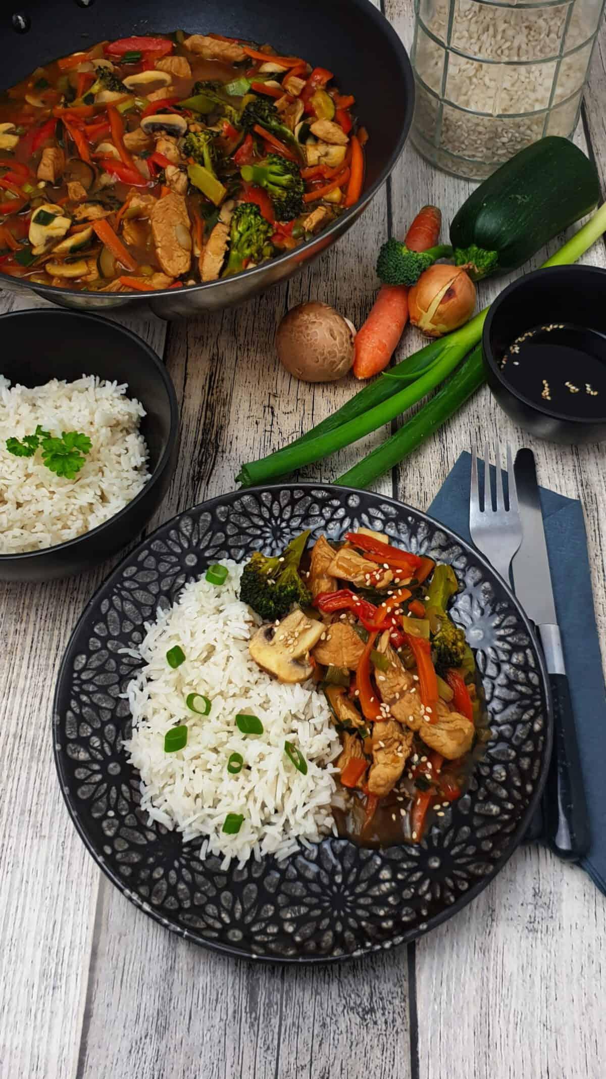 Auf einem dunklen Teller angerichtet Reis mit chinesischer Gemüse-Puten Pfanne. Im Hintergrund Deko.