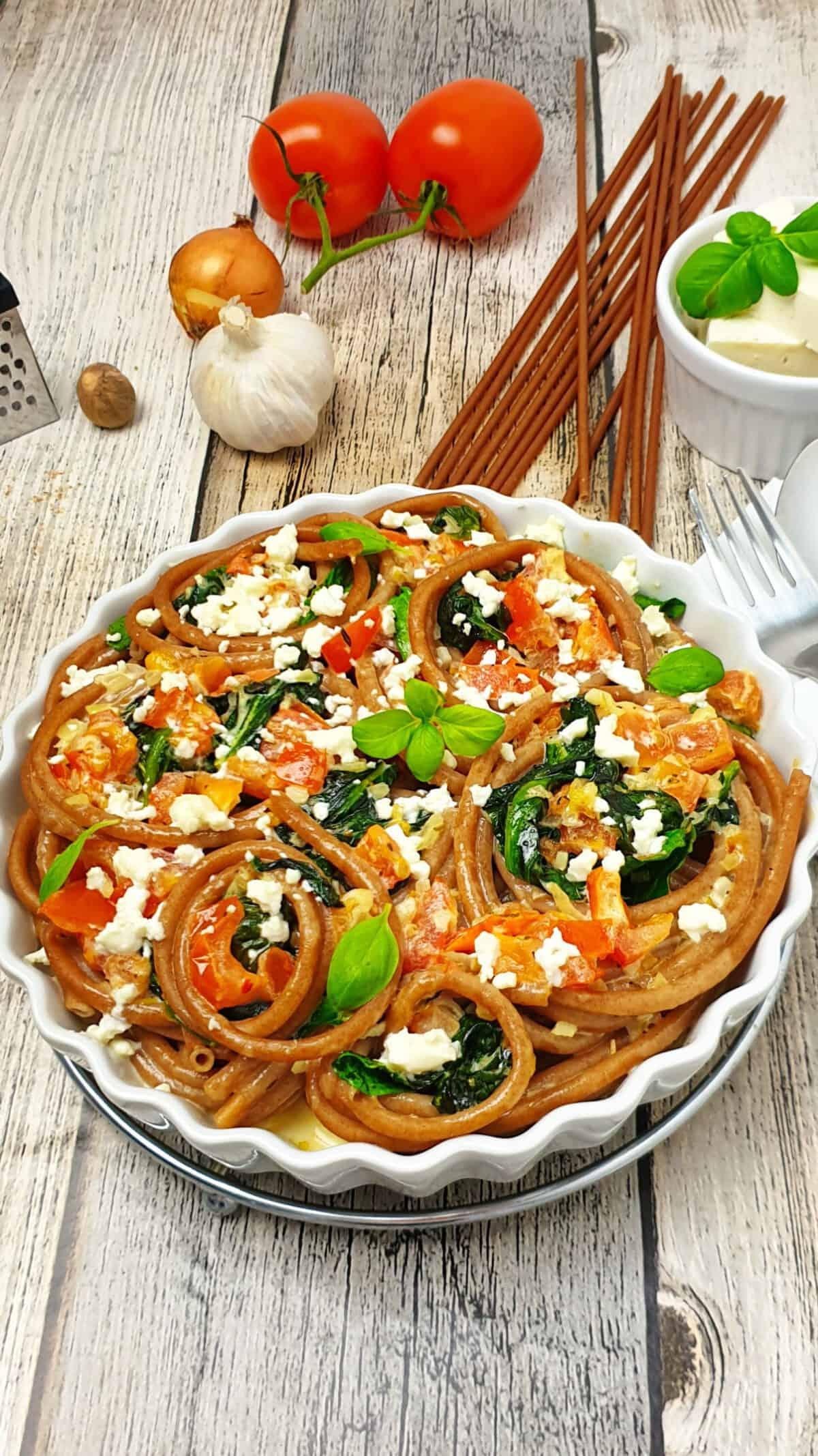 Vollkorn Makkaroni Auflauf mit Spinat und Feta in einer weißen runden Auflaufform.