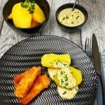 Auf einem schwarzen Teller angerichtet 3 selbstgemachte Fischstäbchen mit Salzkartoffeln und einer Dill-Senf-Soße. Im Hintergrund eine Schale mit Kartoffeln und eine Schale mit Dill-Senf-Soße.