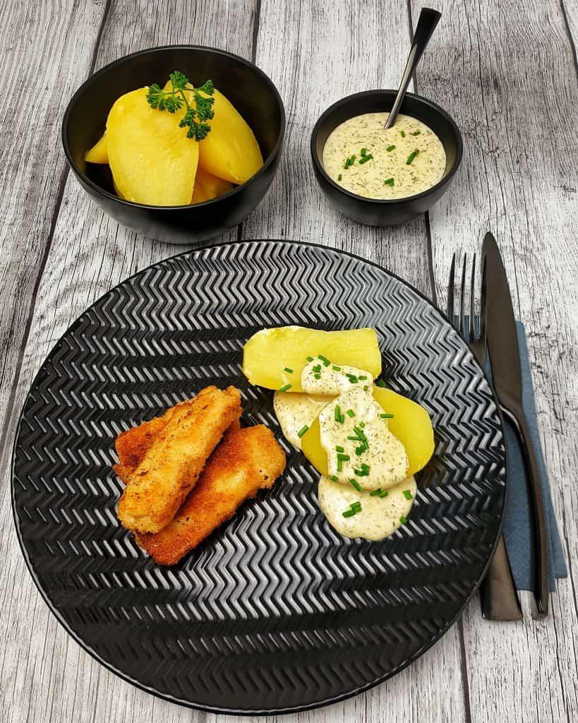 3 selbstgemachte Fischstäbchen mit 3 kleinen Kartoffeln auf einem grauen Teller. Unter und auf den Kartoffeln eine Dill-Senf-Soße. Im Hintergrund eine kleine Schale mit Soße, 2 kleine rohe Kartoffel und eine Zwiebel. Alles dekorativ angerichtet und fotografiert.