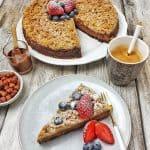 Ein Stück Schokoladen-Kuchen angerichtet auf einem Teller mit frischen Beeren. Im Hintergrund Deko.