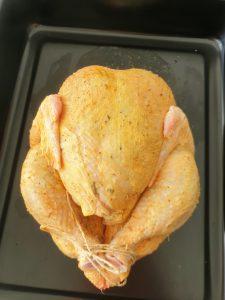 Ganzes Hähnchen/Poularde auf einem Backblech fertig gefüllt und mit Gewürzen und Butter mariniert, fertig zum Backen im Ofen
