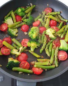 In einer Pfanne angebratene Spargelstücke mit Tomaten und Brokkoli.