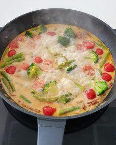 In einer Pfanne Brokkoli, Spargel und Tomaten in einer Soße.