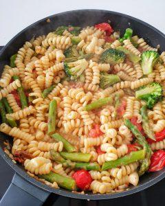 In einer Pfanne Spargel Pasta mit Tomaten in Soße.