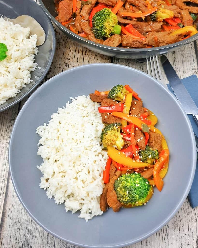 Asiatisches Rindfleisch mit Reis in einer grauen Schale servirt.