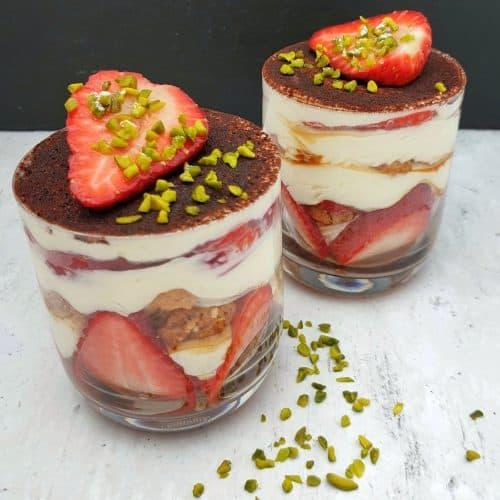 In einem Glas angerichtet Erdbeer Tiramisu mit Pistazien.