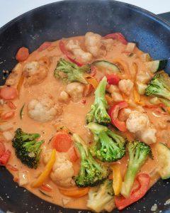 In einer Pfanne angebratenes Gemüse mit Kokosmilch und Curry.