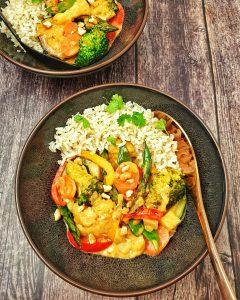 Gemüse-Curry mit Blumenkohl und Brokkoli mit Kokosmilch serviert mit Reis in einer braunen Schale.