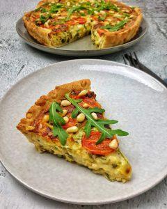 Ein Stück Quiche mit Rucola und Tomaten auf einem hellgrauen Teller. Mit Pinienkernen und Rucola serviert.