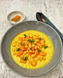 Süßkartoffel-Kichererbsen Suppe mit Kokosmilch in einer grauen Schale angerichtet.