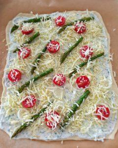 Ein Flammkuchenteig mit Crème fraîche bestrichen und mit grünem Spargel belegt auf einem Backpapier.