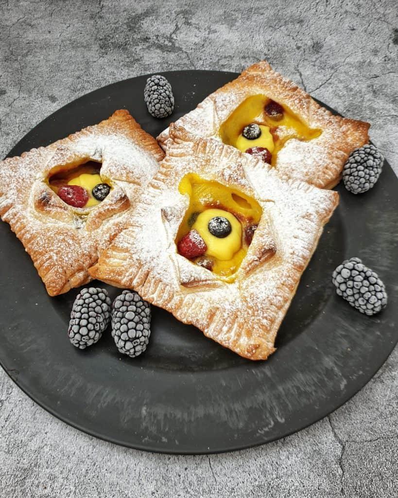 Auf einem dunklen großen Teller drei Blätterteigtaschen mit Pudding und Beeren gefüllt.