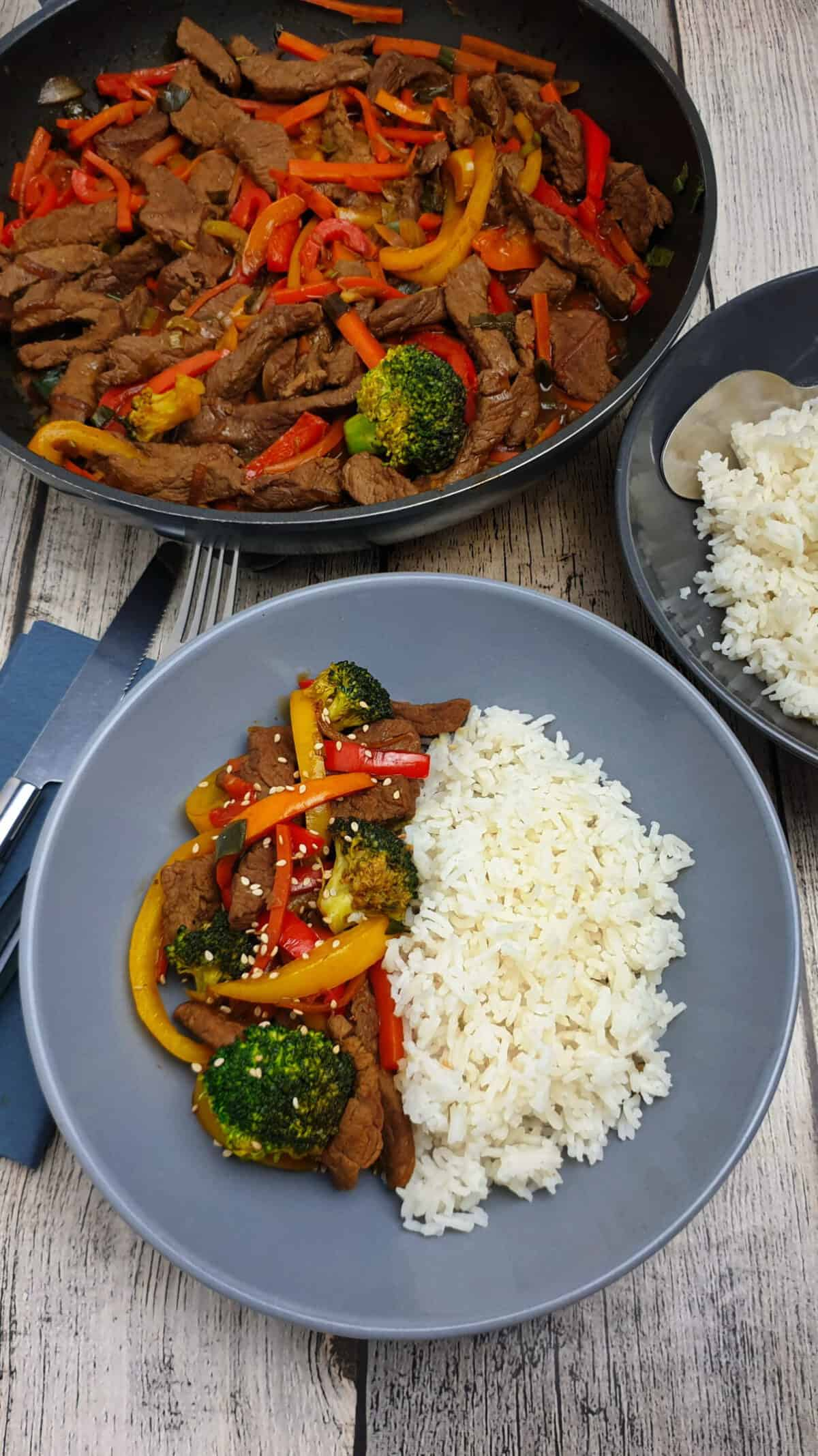 Asia Rindfleisch mit Reis in einer grauen Schale angerichtet. Im Hintergrund eine Pfanne.