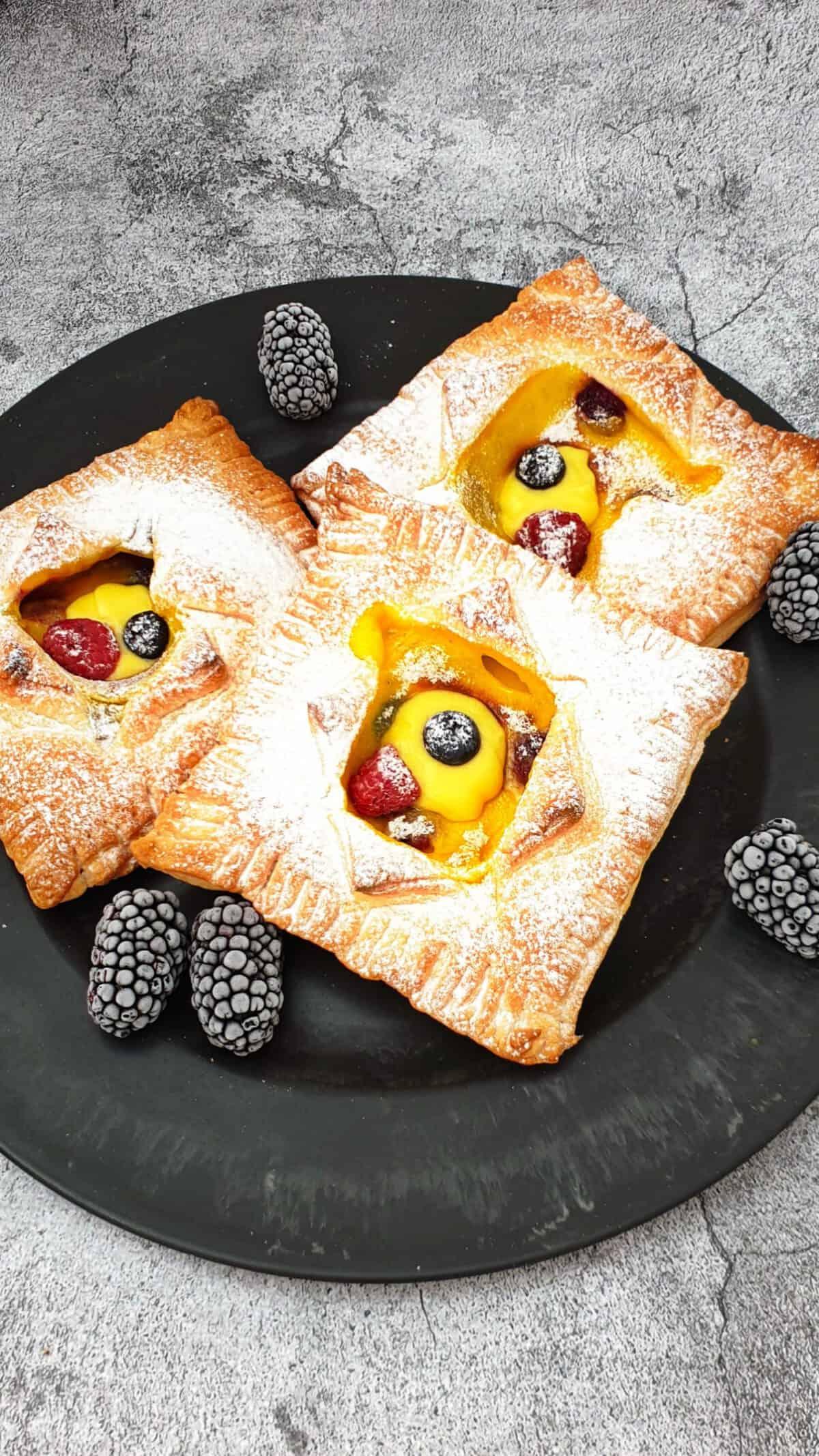 Auf einem dunklen großen Teller drei Blätterteig Teilchen mit Pudding und Beeren gefüllt.