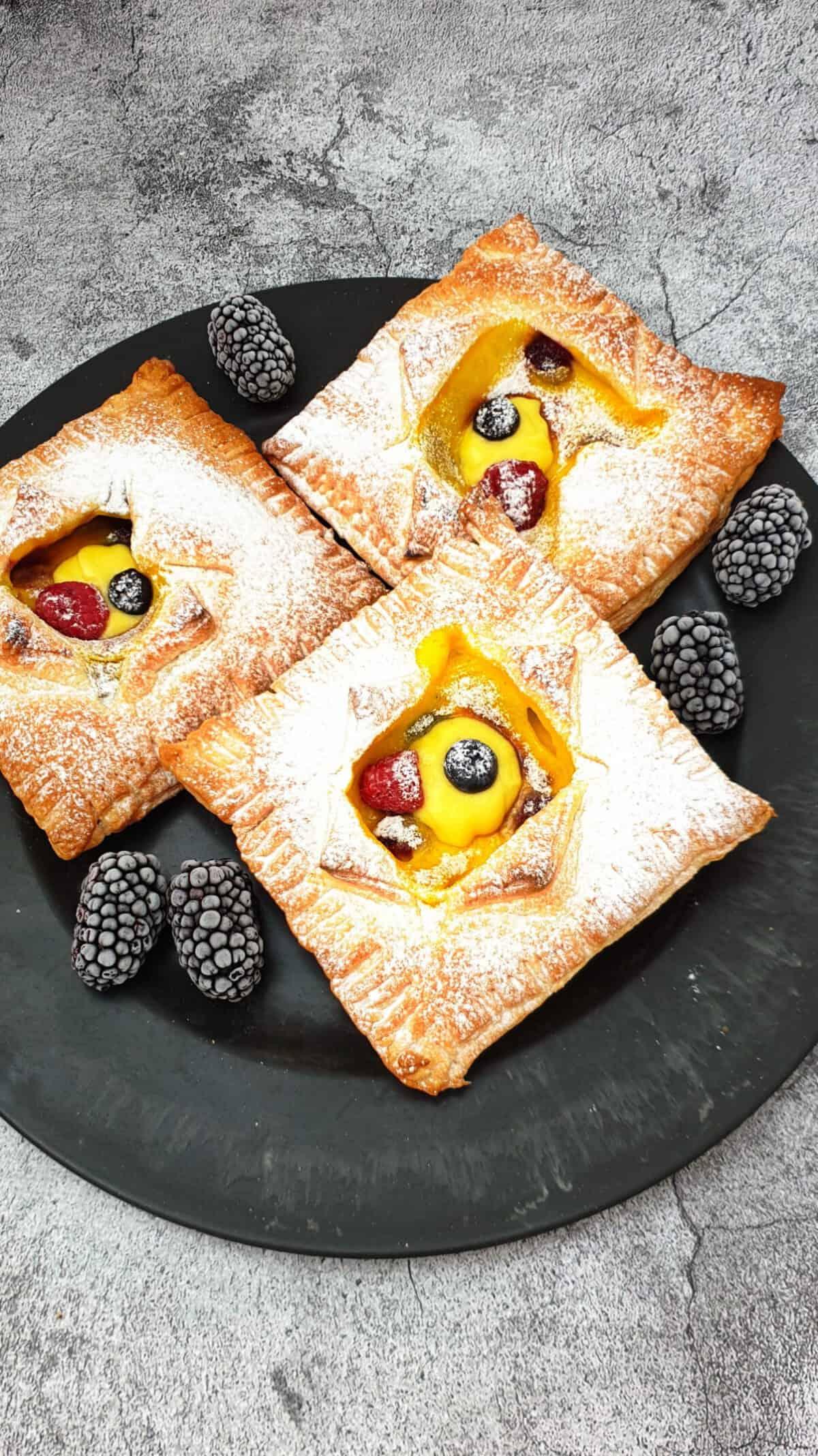 Auf einem dunklen großen Teller drei Blätterteig Taschen mit Pudding und Beeren gefüllt.